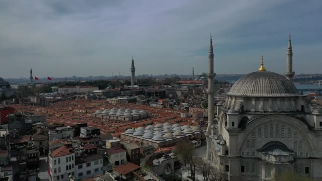 stockvideo's en b-roll-footage met an aerial view from a drone shows nuruosmaniye mosque and the roof of the grand bazaar during turkey's second weekend lockdown imposed to prevent the... - grote bazaar van istanboel istanboel