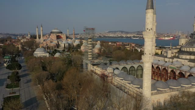 an aerial view from a drone shows old city's monuments blue mosque and hagia sophia and the surrounding area empty during a two-day lockdown imposed... - トルコ点の映像素材/bロール