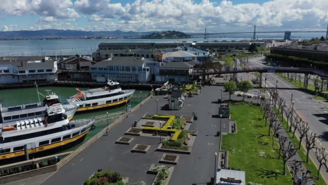 an aerial view from a drone shows streets virtually deserted at the pier 39 tourist destination on march 26, 2020 in san francisco, california. with... - pier 39 san francisco stock videos & royalty-free footage