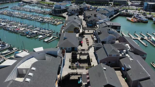 an aerial view from a drone shows streets virtually deserted at the pier 39 tourist destination on march 26 2020 in san francisco california with... - inquadratura fissa video stock e b–roll