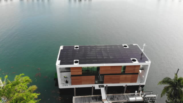 vídeos de stock e filmes b-roll de an aerial view from a drone shows the arkup houseboat a greenenergy luxury floating home that can allow owners to adapt as the sea level continues to... - barco casa