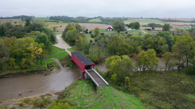 an aerial view from a drone shows the roseman covered bridge that was built in 1883 on october 10, 2019 in winterset, iowa. the 2020 iowa democratic... - überdachte brücke brücke stock-videos und b-roll-filmmaterial