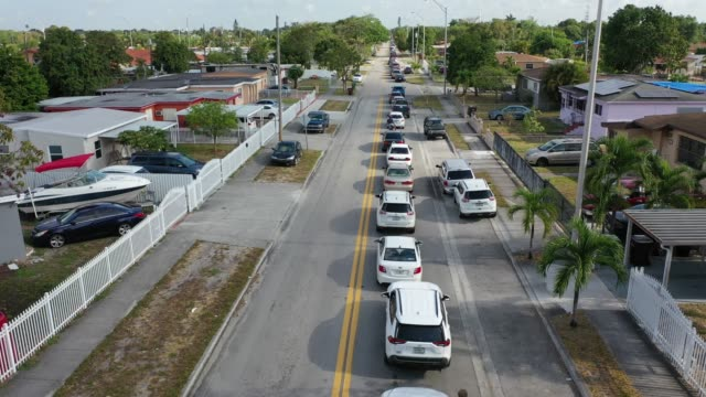 vídeos de stock e filmes b-roll de an aerial view from a drone shows vehicles lining up to receive unemployment applications being given out by city of hialeah employees in front of... - desemprego