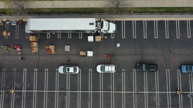 an aerial view from a drone shows volunteers with forgotten harvest loading food into vehicles at a mobile pantry april 14, 2020 in detroit,... - detroit michigan stock videos & royalty-free footage