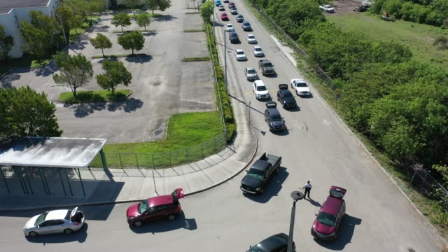 an aerial view from a drone vehicles are seen in two lines as the people inside wait to receive items of food during a food distribution setup at... - hialeah stock videos & royalty-free footage