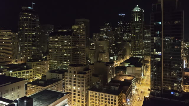 An aerial view nighttime time lapse of downtown Seattle featuring the 1201 3rd Avenue building, with Columbia Tower in the background and city traffic below.