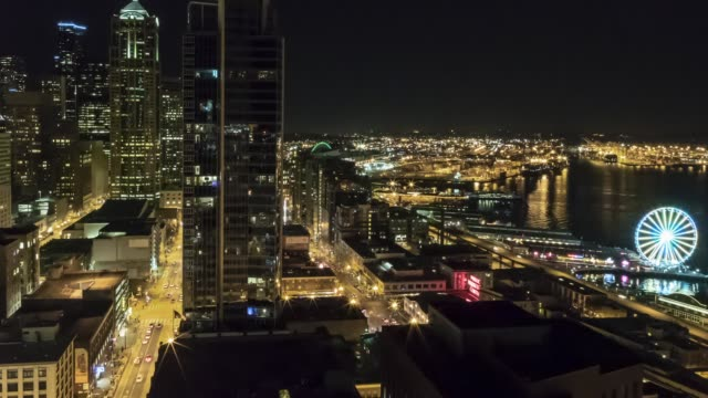 an aerial view nighttime time lapse of the seattle waterfront, featuring two ferries arriving at colman dock simultaneously, with the great wheel clearly visible and the 1201 3rd avenue building and columbia tower in the background. - filiz stock videos & royalty-free footage