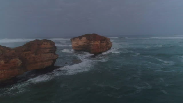 vidéos et rushes de an aerial view of a great ocean road and a lone rock. victoria. australia. - roche sédimentaire