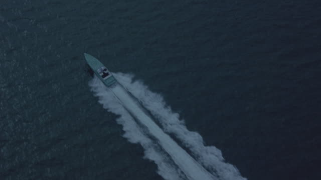 An aerial view of a motorboat moving in an ocean.