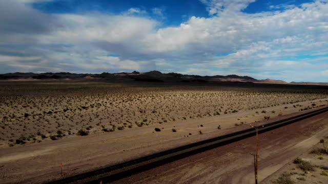 an aerial view of a rail road tracks through the mojave desert on september 22 2019 near newberry springs california california's fourth climate... - deserto mojave video stock e b–roll