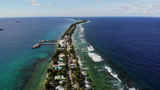vídeos de stock, filmes e b-roll de an aerial view of a strip of land between the pacific ocean and lagoon on november 25.the low-lying south pacific island nation of tuvalu holds about... - south pacific ocean