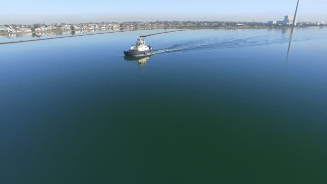 an aerial view of a tugboat at work on glassy waters at sunrise. - david ewing stock videos & royalty-free footage