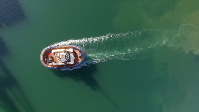 An aerial view of a tugboat at work on glassy waters at sunrise.