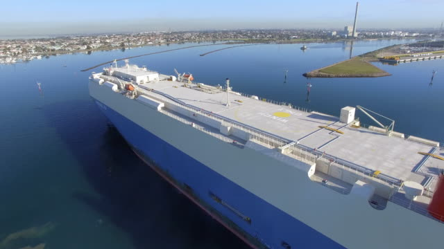 an aerial view of a vehicle carrier approaching a dock being manoeuvred by a tugboat. - david ewing stock-videos und b-roll-filmmaterial