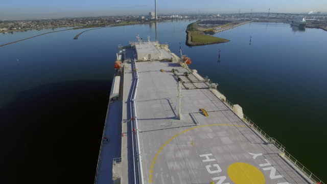 an aerial view of a vehicle carrier approaching a dock on still waters. - david ewing stock videos & royalty-free footage