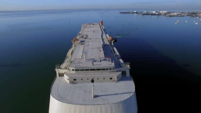 An aerial view of a vehicle carrier approaching a dock on still waters.