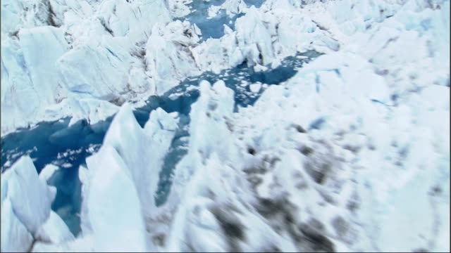 an aerial view of alaska's columbia glacier reveals blue frozen pools filling the crevasses. available in hd. - columbia glacier stock videos & royalty-free footage