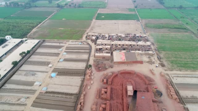vidéos et rushes de an aerial view of brick making factory, plowed fields and agricultural land through drone - pakistan