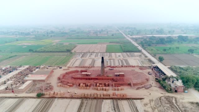 an aerial view of brick making factory, plowed fields and agricultural land through drone - punjab pakistan stock videos & royalty-free footage