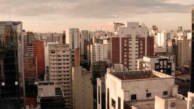 vídeos de stock, filmes e b-roll de an aerial view of buildings low in the street in sao paulo. brazil. - rua