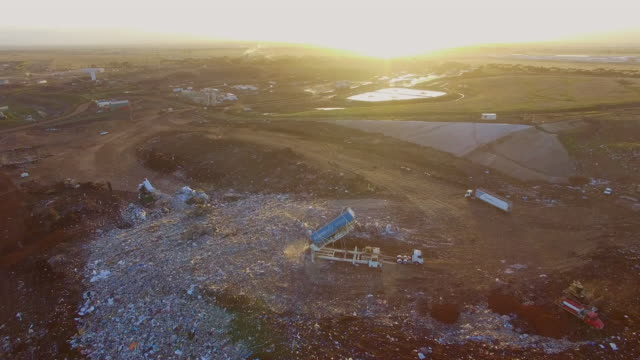An aerial view of bulldozers moving garbage in a landfill site at the Ravenhall Melbourne Regional Landfill site .