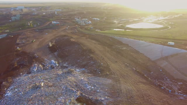 an aerial view of bulldozers moving garbage in a landfill site at the ravenhall melbourne regional landfill site . - david ewing stock videos & royalty-free footage