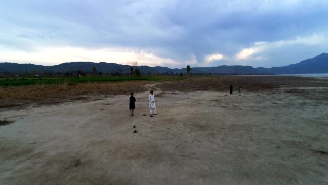 an aerial view of children playing and enjoying on a dry land - pakistan video stock e b–roll
