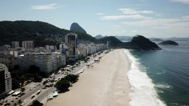an aerial view of copacabana beach amidst the coronavirus pandemic on march 29, 2020 in rio de janeiro, brazil. botafogo beach is usually very busy... - rio de janeiro stock videos & royalty-free footage
