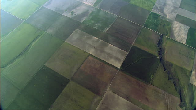 an aerial view of farmlands showing an artistic crop design. - patchwork stock videos & royalty-free footage