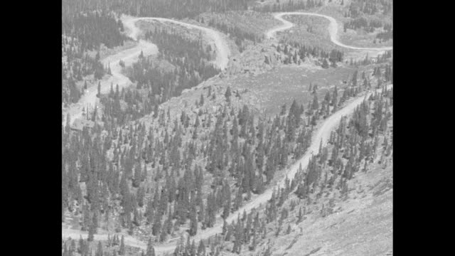 An aerial view of hairpin turns with a solitary car driving them during the Pikes Peak Hill Climb the car skids around a curve past the camera /...
