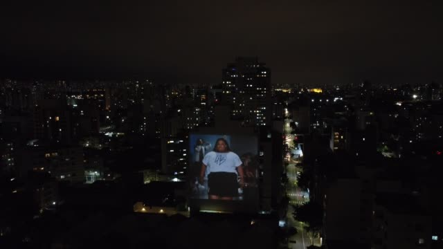 an aerial view of images of models are being projected onto a building in celebration of 25 years of sao paulo fashion week on november 6, 2020 in... - social history stock videos & royalty-free footage