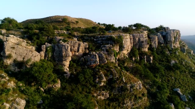 an aerial view of limestone rocks in mountains from drone at sunset - ネイチャーズウィンドウ点の映像素材/bロール