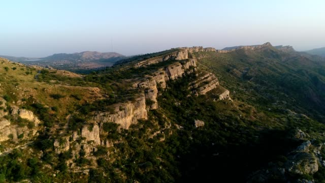 an aerial view of limestone rocks in mountains from drone at sunset - punjab pakistan stock videos & royalty-free footage