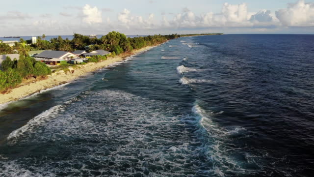 an aerial view of pacific ocean waves breaking along the funafuti shoreline on november 28. the low-lying south pacific island nation of tuvalu holds... - south pacific ocean点の映像素材/bロール
