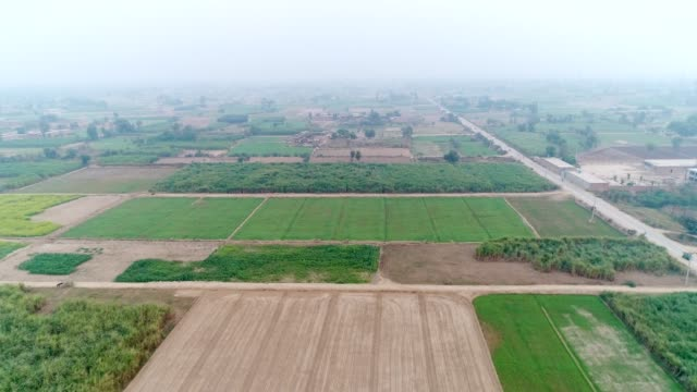 An aerial view of plowed fields and agricultural land through drone