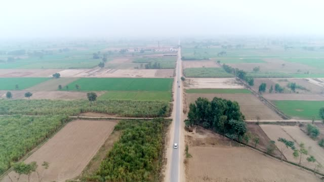 an aerial view of plowed fields and agricultural land through drone - punjab pakistan stock videos and b-roll footage