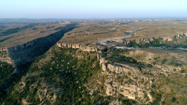 an aerial view of road in lime stone rocky area from drone - pakistan video stock e b–roll