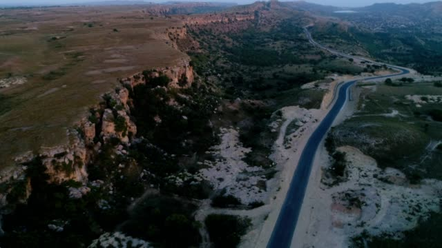 an aerial view of road in lime stone rocky area from drone - punjab pakistan stock videos and b-roll footage