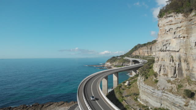 an aerial view of sea cliff bridge in new south wales australia - driving stock videos & royalty-free footage