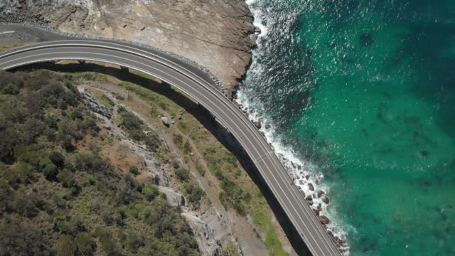 an aerial view of sea cliff bridge in new south wales australia - zweispurige strecke stock-videos und b-roll-filmmaterial