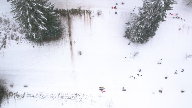 an aerial view of sledders playing in a snow park and sledding down a large snow hill - fatcamera stock videos & royalty-free footage