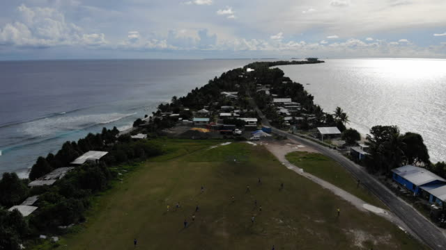 an aerial view of soccer players the lowlying south pacific island nation of tuvalu holds about 11000 people and has been classified as 'extremely... - isole del pacifico video stock e b–roll