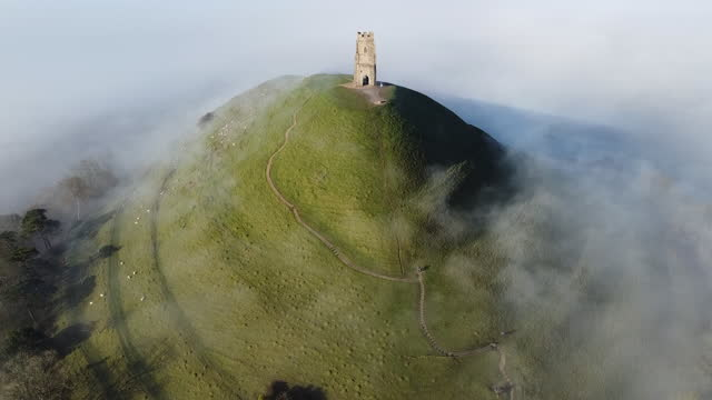 an aerial view of the early morning mist and fog surrounding glastonbury tor is seen from a drone in somerset on february 27, 2021 in glastonbury,... - landscape scenery stock videos & royalty-free footage