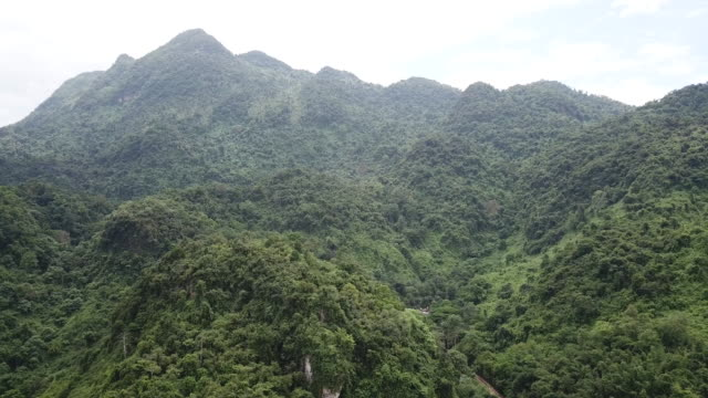 an aerial view of the hills above the cave network where boys among a group of 13 trapped in a flooded cave in khun nam nang non forest park in the... - 洞窟点の映像素材/bロール