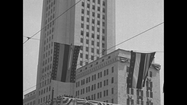 an aerial view of the new los angeles city hall building / pan down of the building decorated with bunting and a color guard marching past / a... - rotes kreuz organisierte gruppe stock-videos und b-roll-filmmaterial