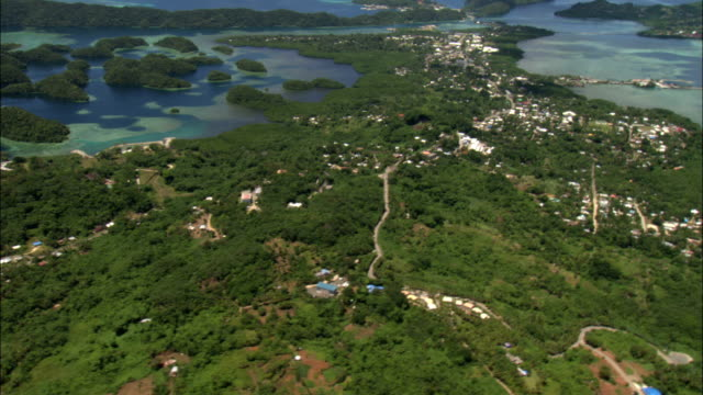 an aerial view of the palau islands reveals homes on wooded hills and blue ocean waters. - palau stock videos & royalty-free footage