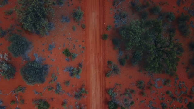 an aerial view of the red centre roads in the australian outback - dirt track stock videos & royalty-free footage
