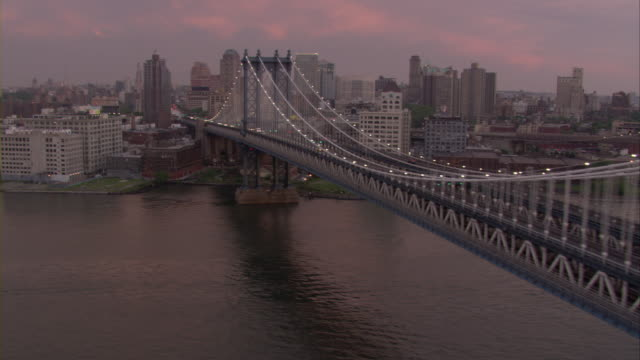An aerial view of traffic moving on the Manhattan Bridge during sunset.