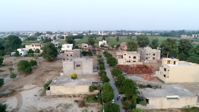 an aerial view of under construction houses in city through drone - punjab pakistan stock videos & royalty-free footage