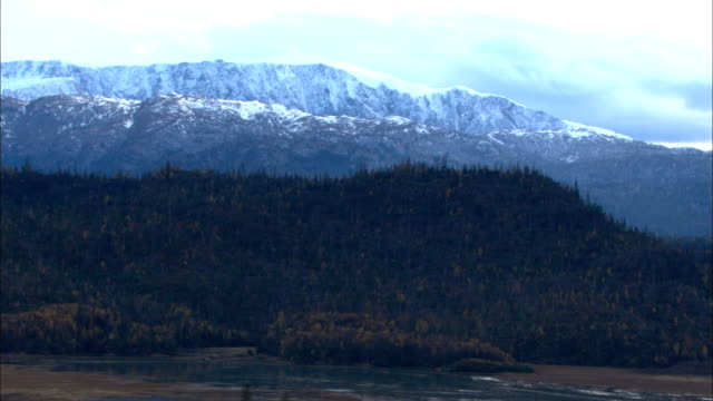 an aerial view over alaska shows marshlands, valleys and rivers under blue skies. - アラスカ点の映像素材/bロール